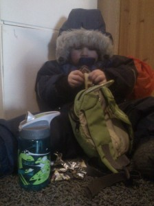 Lillebror nyter siste rest av tursjokoladen, hjemme i gangen.